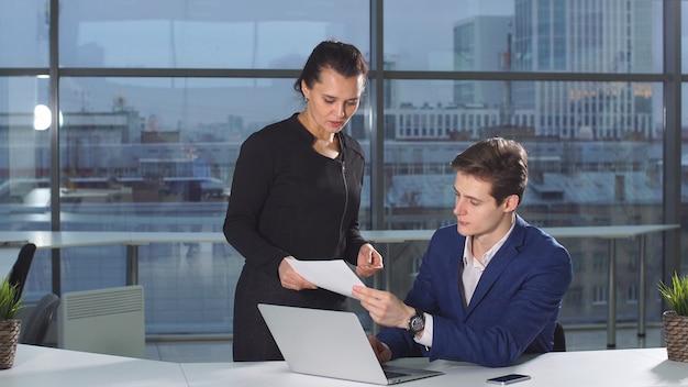 会社の忙しい女性従業員が上司に財務書類を持ってくる