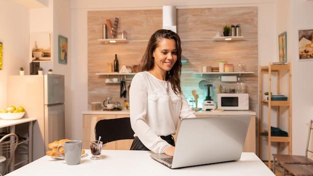 仕事のための企業プロジェクトに取り組むためにラップトップを使用して家庭の台所で忙しい女性。夕方の深夜にノートブックを使用して家庭の台所に集中した起業家。