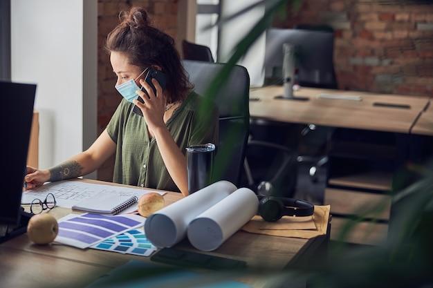 보호용 마스크를 쓴 바쁜 여성 인테리어 디자이너는 전화 통화를 하고 메모를 작성합니다.