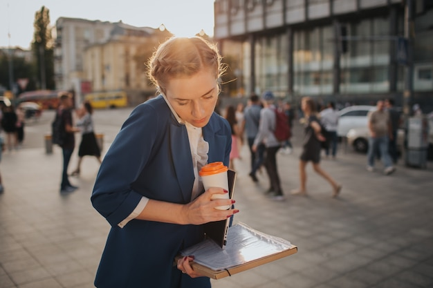 Busy woman is in a hurry, she does not have time, she is going to eat snack on the go. worker eating, drinking coffee, talking on the phone, at the same time. businesswoman doing multiple tasks.