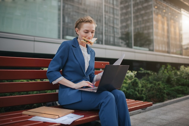 Busy woman is in a hurry, she does not have time, she is going to eat snack outdoors. worker eating and working with documents on the laptop at the same time.