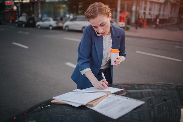 Занятая женщина спешит, у нее нет времени, она собирается разговаривать по телефону на ходу. предприниматель делает несколько задач на капоте автомобиля. многозадачность делового человека.