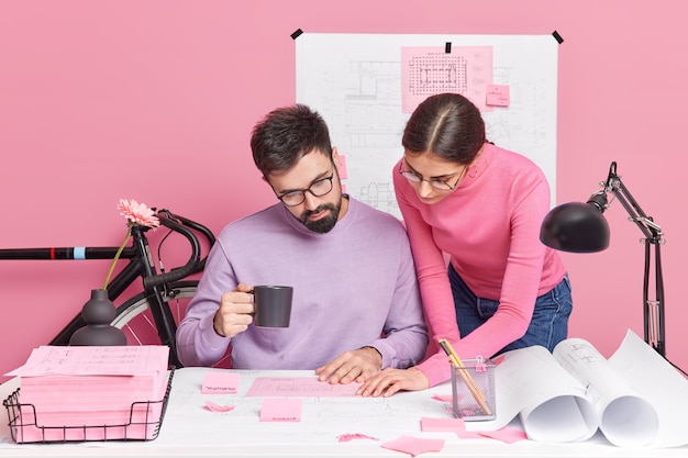 Busy woman and man office workers have brainstorming session share ideas for homework project pose in coworking space pose at desktop with blueprints around communicate together at office company