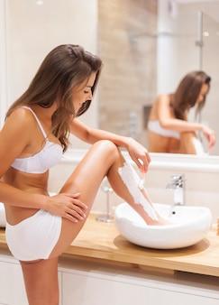 Busy woman shaving legs in sink of bathroom