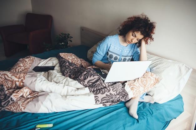 Занятая женщина с вьющимися волосами, работающая за ноутбуком в постели
