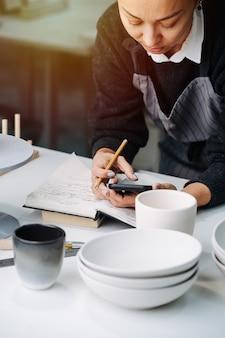 새로 생산 된 빈 식기 및 도구로 테이블 뒤에서 일하는 바쁜 여자