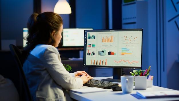Donna impegnata che lavora di notte davanti al computer che prende appunti scrivendo sui rapporti annuali del taccuino, controllando il progetto finanziario. dipendente concentrato che utilizza la rete tecnologica senza fili che fa gli straordinari per lavoro