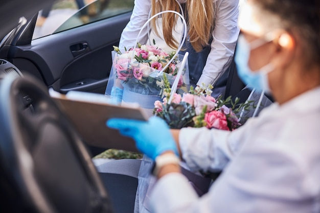 차로 꽃다발을 배달할 준비를 하는 바쁜 여성