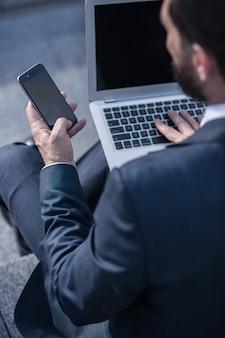 忙しい仕事。彼のラップトップとスマートフォンを使用してプロの集中ビジネスマン