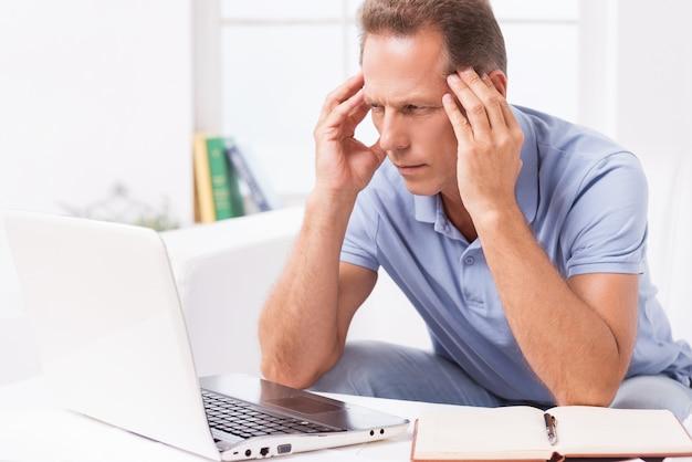 家で忙しい。ノートパソコンを見て、自宅のソファに座っている間、手で頭を保持している欲求不満の成熟した男