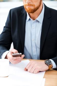 바쁜 일. 그의 작업 장소에 앉아있는 동안 시계를 착용하고 휴대 전화를 들고 수염 사업가의 근접