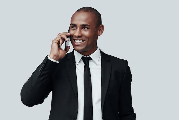 바쁜 근무일. 정장 차림의 매력적인 젊은 아프리카 남자는 스마트 폰으로 통화하고 회색 배경에 서서 웃고 있습니다.