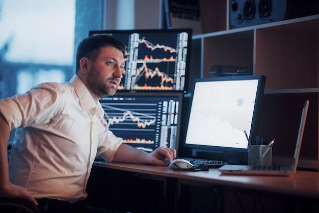 忙しい一日。クリエイティブオフィスの机に座ってモニターを見ている青年実業家のクローズアップ。