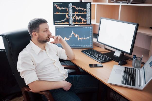 Напряженный рабочий день. крупный план молодого бизнесмена, смотрящего на монитор, сидя за столом в творческом офисе.