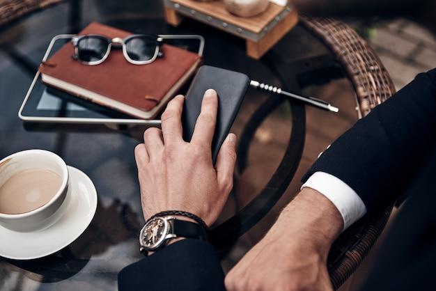바쁜 근무일. 야외 레스토랑에 앉아 있는 동안 약간의 커피 휴식을 취하는 스마트 캐주얼 차림의 젊은 남자의 꼭대기를 클로즈업