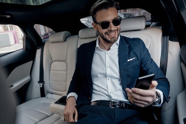 바쁜 근무일. 정장 차림의 잘생긴 청년은 차에 앉아 스마트폰을 보고 웃고 있다