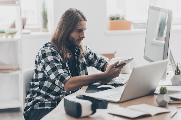忙しい一日。創造的なオフィスで彼の机に座っている間デジタルタブレットに取り組んでいる長い髪のハンサムな若い男