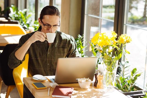 바쁜 근무일. 그의 일에 집중하면서 커피 한 잔을 마시는 심각한 잘 생긴 남자