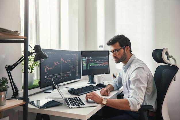 Занятый рабочий день молодой бородатый торговец в очках работает с ноутбуком, сидя в своем