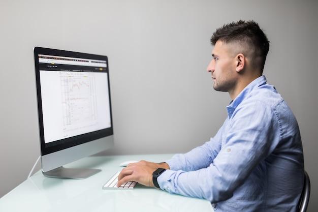 Напряженный рабочий день. молодой бородатый трейдер, работающий с ноутбуком, сидя в своем современном офисе перед экранами компьютеров с торговыми графиками.