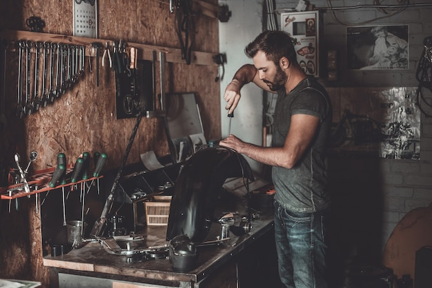 Busy working in repair shop. confident young man using work tool while working in repair shop