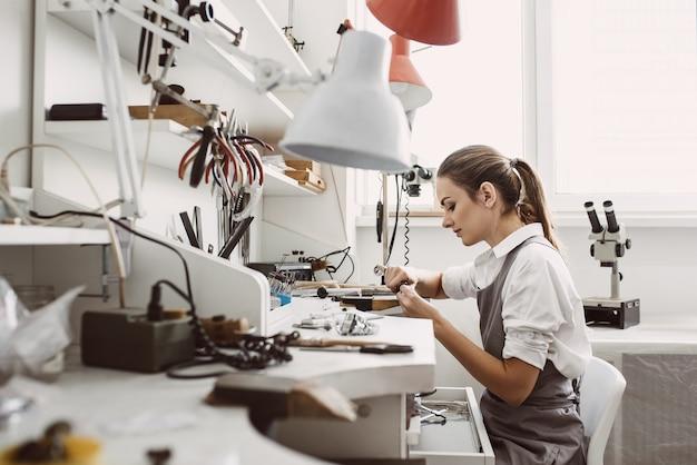 바쁜 일. 그녀의 작업대에서 새로운 보석 제품을 작업하는 젊은 여성 보석상의 측면. 주얼리 제작 과정. 사업. 보석 작업실. 작업 과정. 보석 제조 개념