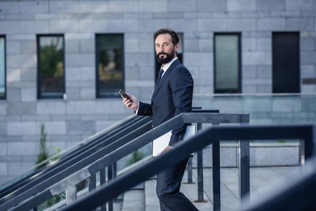 忙しい世界。階段を降りながらスマートフォンを持って楽しいプロのビジネスマン