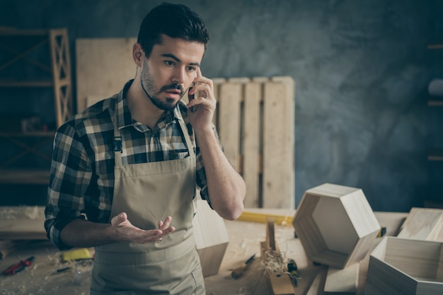 Busy worried overloaded foreman handyman speak on smartphone have problems with clients decide offers furniture construction restoration repair orders in home workplace