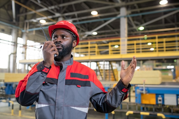 공장에서 워키 토키를 사용하여 동료에게 작업을 설명하는 동안 손짓을하는 바쁜 젊은 아프리카 계 미국인 노동자