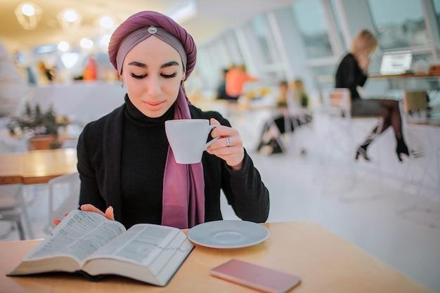 바쁜 젊은 아라베인 여성은 책을 읽고 커피를 마신다. 그녀는 그림을 돌리고 있습니다. 그녀는 옆에 앉는다. 여자는 바쁘다