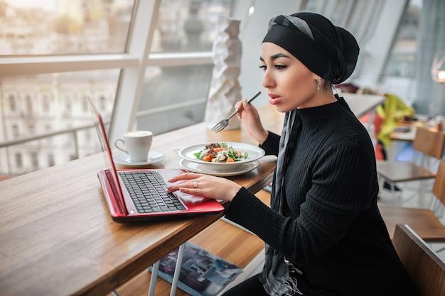 忙しい若いアラビアの女性はラップトップで働いて、それを見てください。彼女は中に座って、食べ物を入れたボウルにフォークをかざします。モデルはヒジャーブを着ています。