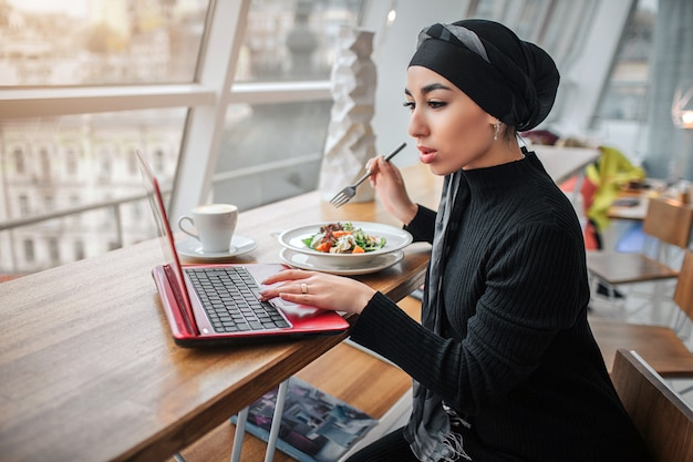 Busy young arabian woman work at laptop and look at it. she sits inside and hold fork upon bowls with food. model wears hijab.