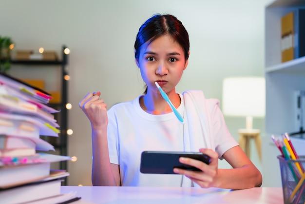 바쁜 젊은 아시아 여성이 이를 닦고 스마트폰으로 온라인 게임을 하고 있습니다.