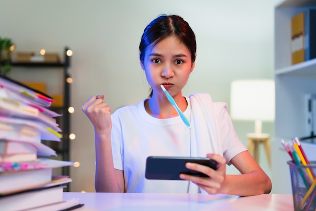 Busy young asian woman brushing teeth and hand playing online game on smartphone.