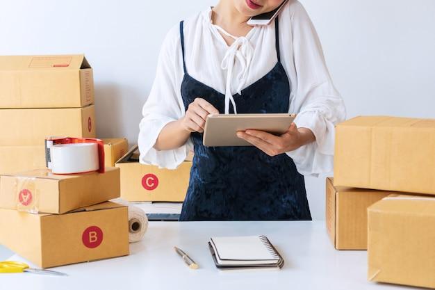 忙しい若いビジネス起業家がタブレットで在庫バランスを確認しながら顧客と電話で話しています。