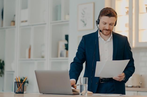 Занятый молодой бизнесмен в формальной одежде и гарнитуре, анализирующий отчет во время конференции по видеочату, держа документ, стоя на своем рабочем месте дома