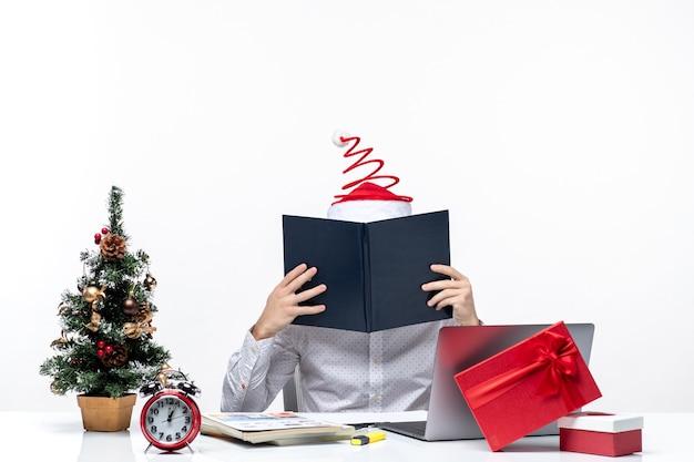 Занятый молодой бизнесмен с забавной шляпой санта-клауса, проверяющей информацию в документах в офисе на белом фоне