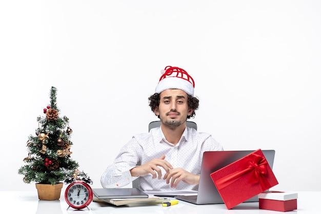 Занят молодой бизнесмен с забавной шляпой санта-клауса позирует перед камерой в офисе на белом фоне