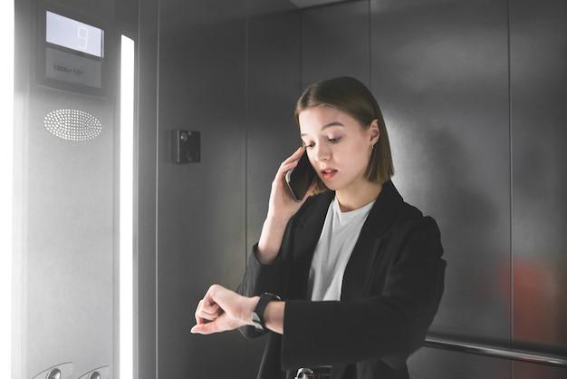바쁜 젊은 사업가 그녀의 시계를보고 엘리베이터에서 전화를 얘기하고 있습니다.