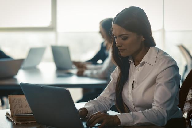 Занят молодой предприниматель, используя интернет на офисном ноутбуке. работающая женщина в чате в компьютерном приложении или