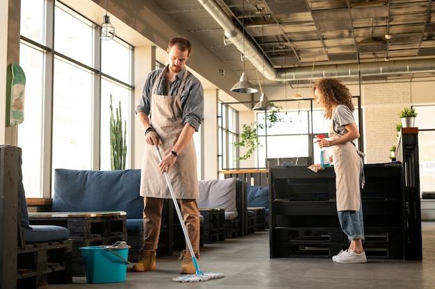 열기 전에 카페를 준비하는 동안 앞치마 바닥을 세척하고 세제로 표면을 청소하는 바쁜 젊은 부부