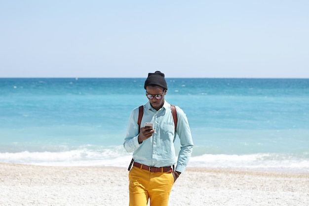 Busy young dark-skinned european man wearing fashionable trendy clothing and backpack staying online even during vacations, using mobile phone on beach, ignoring all beauties that surround him