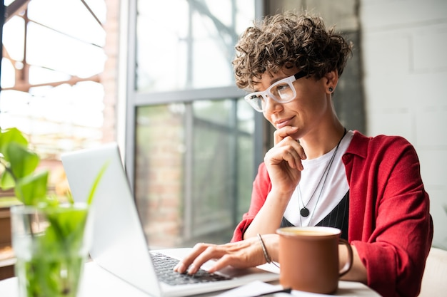Занятая молодая элегантная женщина в очках смотрит на дисплей ноутбука, нажимая клавиши клавиатуры во время работы