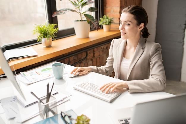 Занятый молодой сотрудник в формальной одежде с помощью клавиатуры и мыши, глядя на экран компьютера на рабочем месте