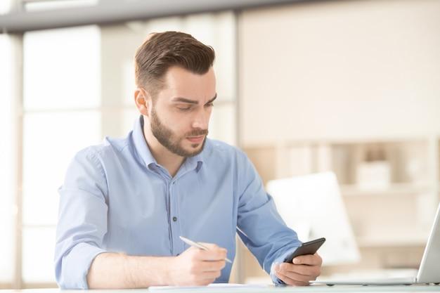 Занятый молодой сотрудник прокручивает или обменивается сообщениями в смартфоне, планируя работу за столом в офисе