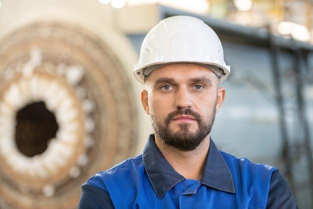 Занятый молодой заводской рабочий в комбинезоне проверяет рабочий файл на планшете во время работы в промышленности