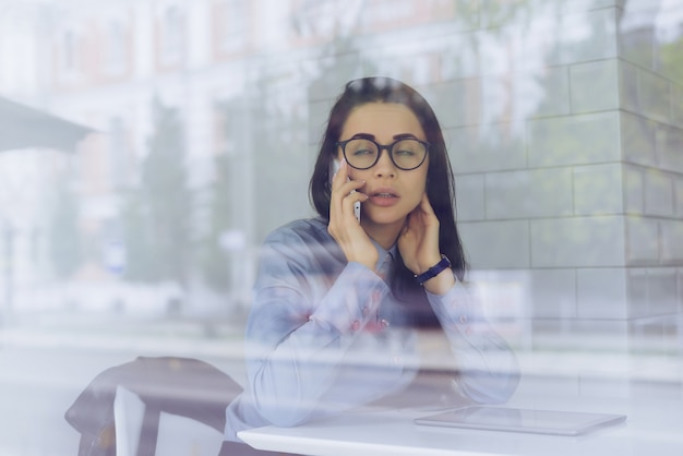 Busy young girl freelancer in blue shirt and glasses is negotiating by phone