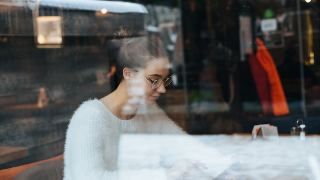 Busy young girl student in a white jacket and wearing glasses sitting in a cafe after studying