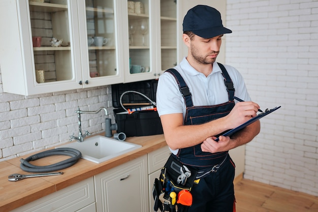 Busy young handyman stands in kitchen