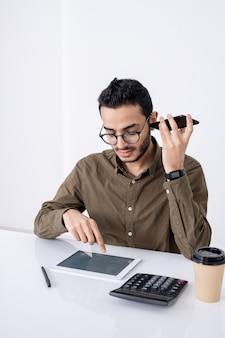 Занятый молодой бухгалтер-мужчина со смартфоном за ухом, указывая на тачпад, делая расчеты за столом
